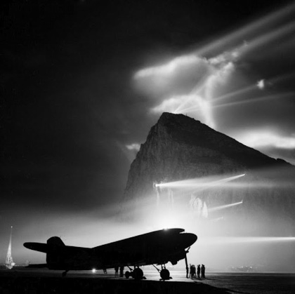 A-Douglas-Dakota-of-the-British-Overseas-Airways-Corporation-at-Gibraltar-silhouetted-by-searchlights-on-the-Rock-1940-45.jpg